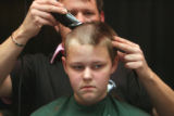 Seventh grade student Brianna Persinger (cq) gets her head shaved by volunteer Ken Reed (cq) when...