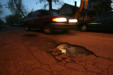 A motorist drives past a pothole on Sherman St., between Alameda and Dakota, Wednesday evening...