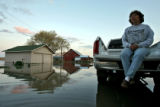 DLM0096  Water surrounds Marilyn Hilzer, 61, as she sits on the tailgate of her pick-up at 11056...