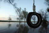 DLM0204  A tire swing hangs in Marilyn Hilzer's flooded yard in front of her  farmhouse at 11056...