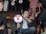 Patrick Wu, holding number  bids 5 million dollars during an auction for the McAfee estate...