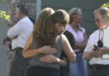 A woman and young man hug, center of frame. (the fire marshal identified them as the mother and...