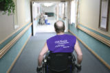 56 year-old Nicholas Patrick wheels himself down the hall at Hallmark Nursing Center in Denver on...