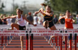 Kelly Coomes, cq, center, of Rampart, strides over the second to last hurdle during her heat of...