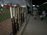 Wood bats hang on a fence in the dugout of the Denver Academy baseball team, while playing Platte...