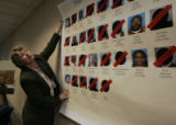 Beverly Walz with the Rocky Mountain High Intensity Drug Traffic Area hangs a display of suspects...