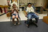 Jacqueline Allala, 5, and Jesus Valencia, 6, sit with wigs on playing roles in a small play as...