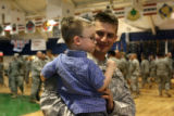 Sgt. Scott Rayl, cq, of Colorado Springs carries his one of his two children Collin Rayl, 2, after...