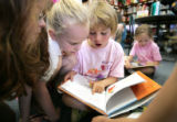 "(L-R) Jeannine Ochtera,5, Isabella Encinas, 5, and Noelle Bland, 6  read "" I Love You Stinky..."