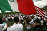 DLM0696  Pedro Rodriguez, 52, holds both an American and a Mexican flag as he listens to the...