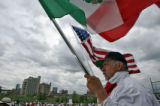 DLM0721  Pedro Rodriguez, 52, holds both an American and a Mexican flag as he listens to the...
