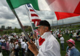 DLM0655  Pedro Rodriguez, 52, holds both an American and a Mexican flag as he listens to the...