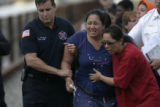 0390 Denver Fire Chief Larry Trujillo, left, supports Elsha Guel, center, mother of Jose Matthew...