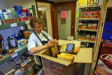 Volunteer Karol Randolph (cq) checks the expiration date on food before putting it on shelves on...