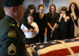 MJM072 Staff Sergeant Eric Barb (cq), left, helps push in the coffin of PFC Seth M. Stanton of...
