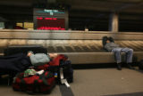 MJM1713  Lauren Harrison (cq), 18, left, sleeps in the baggage claim area Thursday morning at...