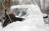Kreesha Franklin (cq), 12, of Denver tries her best to clear the family minivan of snow Thursday...