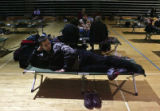 Bertran Fritschka (cq), from Germany, rests on a cot while stuck in the temporary shelter in the...