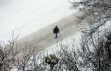 A pedestrian walks north on a plowed portion of Broadway near 14th Avenue early  December 21, 2006...