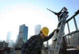 MJM058   Engineer, Tim Olsen (cq), works on installing one of two AirX model windmills made by...