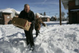 Jay Gould and fiancee Marge Conner trudge through the snow to give food boxes to the needy on...