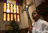 MJM036  Altar boy, Uche Agwu, 11, holds a crucifix Sunday morning prior to a 9 a.m. mass at St....