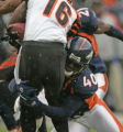 In the first quarter,  Denver Broncos safety Curome Cox, right, stops a run by Cincinnati Bengals...