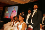 Beaus stand and escorts sit as the event co-chairs, Dierdre McGee (screen, left) and Angela...