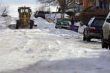 A road grader tries to scrape some of the compacted snow from a side street in the Barnum West...