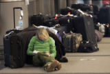 (CODER101) While her parents search for a missing bag, Erin Etzler, 20, from Chicago, leans...