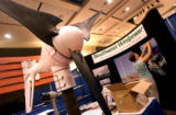 Ketter Foutz-Ulrich of Southwest Windpower wind power constructs a booth displaying the companies...