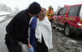 A paramedic from AMR examines a motorist injured in a 25 car pile up, on north bound I-25 at the...