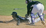Colorado Rockies catcher #55 Alvin Colina, right, tags out Chicago White Sox outfielder, #64,...