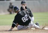 Colorado Rockies' Troy Tulowitzki misses a tag at second base due to an errant throw by the...