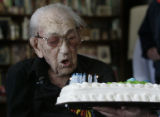 Reuel Millar blows out the candles on his birthday cake --he is 110 today at his home in Lakewood,...