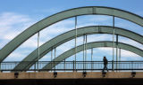A man enjoys the nice weather as he walks across a Speer Blvd. bridge, goes over Little Raven St....