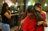Grandmother Carol Martin (cq), right, hugs family friend Rebecca Romero, center while Dandrea...