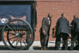 Funeral Director Ronald L. Jones (CQ) , left, gives instructions on lifting the casket of Denver...