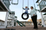 DLM1993  Andrea Thurber pushes her two-year-old daughter, Brianna, on a tire swing at The...
