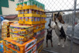 DLM1524  Two dogs bark as cases of donated pet food are dropped off at the Colorado Humane Society...