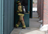 A firefighters  enters an area at Evergreen High School Tuesday morning March 6, 2007 where a fire...