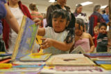 Jacquelyn Casillas, 4 years old, looks through a table covered with free books Tuesday morning...