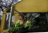 Lynn Sojak (cq) leaves City Floral carrying a tray of cold tolerant plants in Denver, Colo....