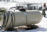 Yolanda Welch (cq) walks past an empty propane tank at  her farmhouse, February 15, 2007 in...