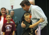8 year-old Garrison Hayes (cq), a young cancer survivor, hugs Ted Carlton, an employee from...