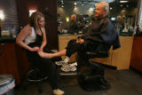 Catrina, (cq), (first name only by her request) listens to and finishes a pedicure for Brad...