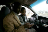 A brief moment between father and son is interupted by a phone call as Daniel Negash (cq) a Denver...