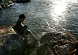 Eddie Vega, 7 of Lakewood tests the water at Confluence Park on Monday, March 12, 2007 in Denver,...