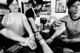 Employees at the Cutthroat Cafe holds out their arms with arm bands for Emily Keyes including...