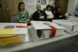 Victim services workers sit behind 4 very large three ring sealed binders of compiled evidence...